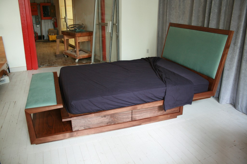 A queen-size bedframe in Black Walnut with upholstered headboard and bench.